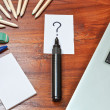 Question mark over a black pen on writing desk — Stock Photo #5439113