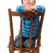 Little boy sits in chair with his eyes closed — Stock Photo