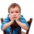 Sad boy sitting on chair — Stock Photo