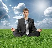 Businessman in lotus pose outdoors — Stock Photo