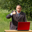 Man with red laptop working outdoors — Stock Photo #6184815