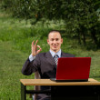 Man with red laptop working outdoors — Stock Photo #6184824