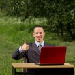 Man with red laptop working outdoors — Stock Photo #6184828