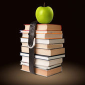 Books pile with belt and apple — Stock Photo