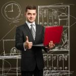 man in pak met laptop in zijn handen — Stockfoto