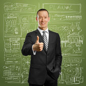 Asian businessman in black suit shows well done — Stock Photo