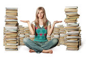 Woman in lotus pose with many books near — Stok fotoğraf