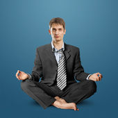 Businessman in lotus pose — Stock Photo