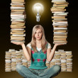 Woman in lotus pose with many books in her hands and bulb — Stock Photo
