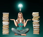 Woman in lotus pose with many books near and bulb — Stock Photo