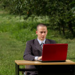 Man with red laptop working outdoors — Stockfoto