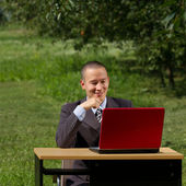 Man with red laptop working outdoors — Stock Photo