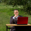 Man with red laptop working outdoors — Stock Photo #6741122
