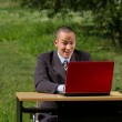 Man with red laptop working outdoors — Stock Photo #6741129