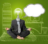 Lamp-head businessman in lotus pose with speech bubble — Stock Photo