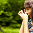 Charming dark-haired woman making herself up at summer green park — Stock Photo