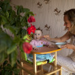 Mother feeding hungry baby in the highchair indoors — Stock Photo