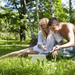 Royalty-Free Stock Photo: Couple using a laptop outdoors and looking happy