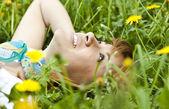Happy woman lying outdoor in dandelion meadow — Stock Photo