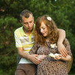 Man hugging his pregnant wife - Stock Photo