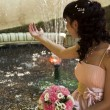 Beautiful bride with flowers near the fountain - Stock Photo
