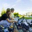 Little girl and mother feeding pigeons urban blue-gray — Stock Photo