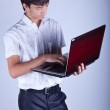 Handsome young man holding a laptop — Stock Photo