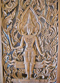 A Deva statue , wood door — Stock Photo