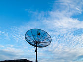 Satellite dish with blue sky background on middle roof — Stock Photo