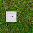 Green energy concept: electric outlet on a grass — Stock Photo