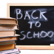 Back to school written on chalkboard with books — Stok fotoğraf