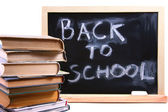 Back to school written on chalkboard with books — Stock Photo