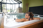 Back side of a young woman relaxing on a big spa — Stock Photo