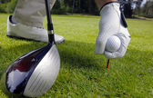 Hand placing a tee with golf ball — Photo