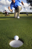 Ball rolling into the hole — Stockfoto