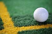 White golf ball on training mate — Stock Photo
