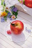 Red apple on white garden table — Stockfoto