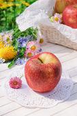 Red apple on white garden table — Stock Photo