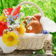 A basket with patties and flowers in the garden - Stock Photo