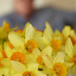 Beautiful daffodils indoor in front of an unidentifiable woman — Stock Photo #6545001