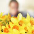 Beautiful daffodils indoor in front of an unidentifiable woman — Stock Photo #6545238