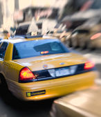 Motion and lens blurred taxi or cap — Stock Photo