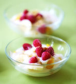 A photo of dessert - raspberries, banana and cream — Stock Photo