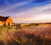 Old farmhouse in sunset — Stock Photo