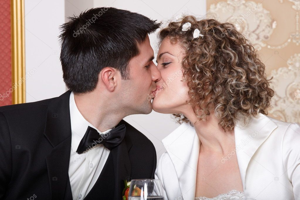 Bride and groom kissing at the wedding table  Stock Photo #6073766