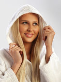 Blond girl in a white bathrobe smiling, closeup — Stock Photo