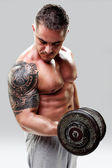 Bodybuilder with a tattoo lifting weights, closeup — Stock Photo