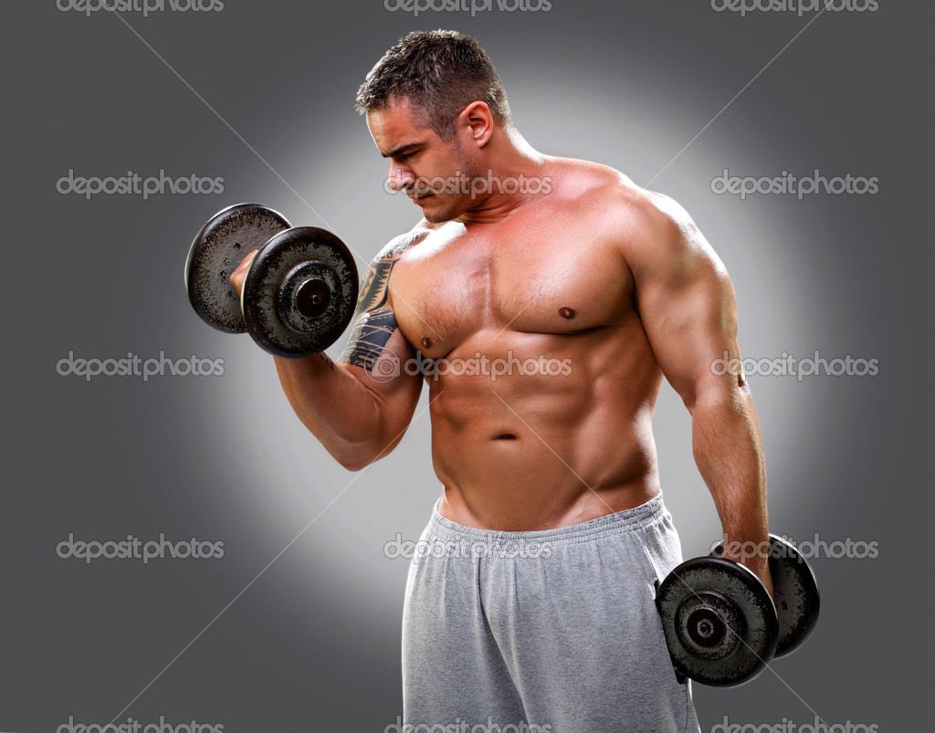 Bodybuilder with a tattoo lifting dumbells, closeup 2 - Stock Image