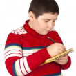 Boy who writes on a notepad - Stock Photo