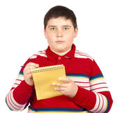 Boy who writes on a notepad — Stock Photo